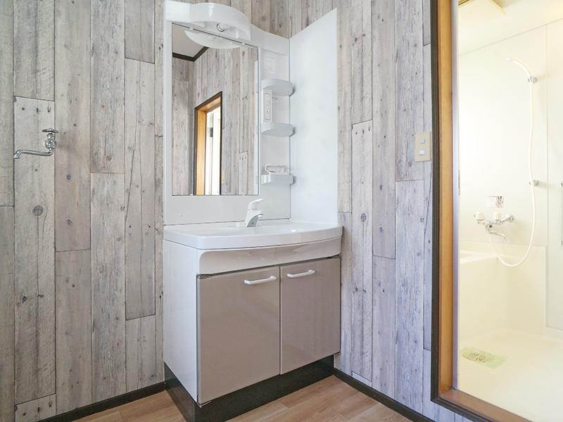シャワーヘッド付きの洗面台。ホワイトウッドのモダンな壁紙です♪